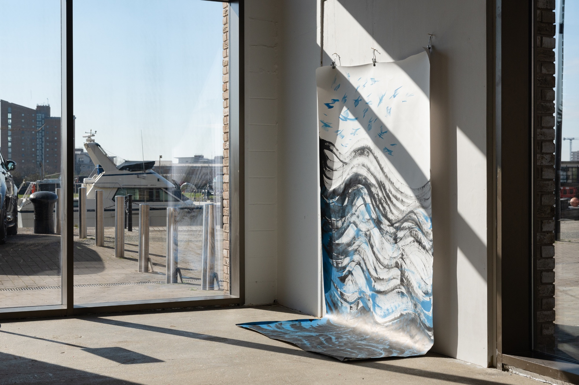 Large abstract painted scroll hung up in window with dock view outside