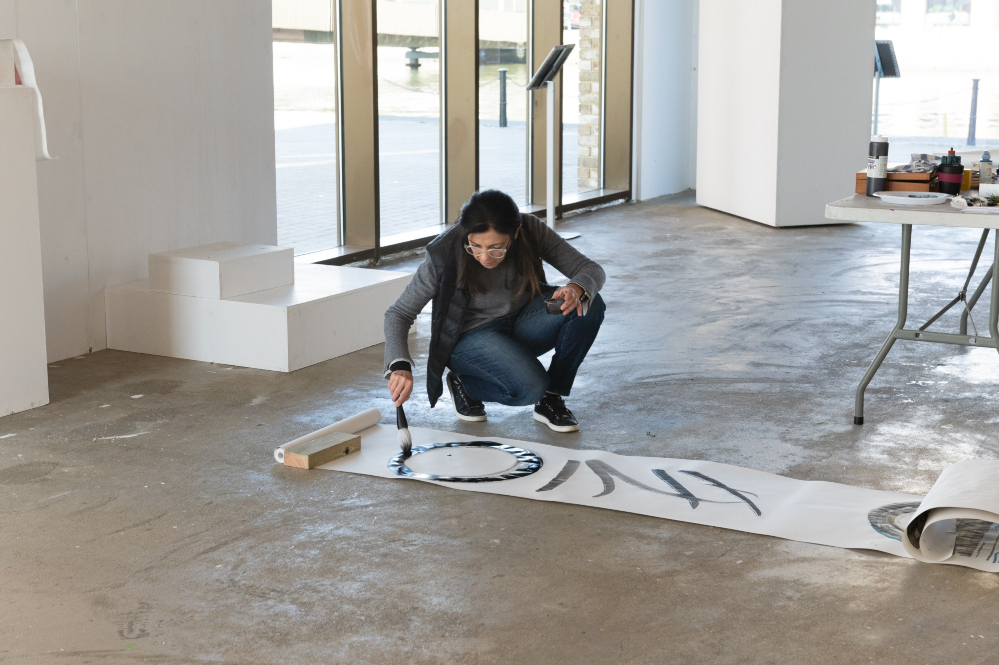Artist bending over to work on a scroll on the floor