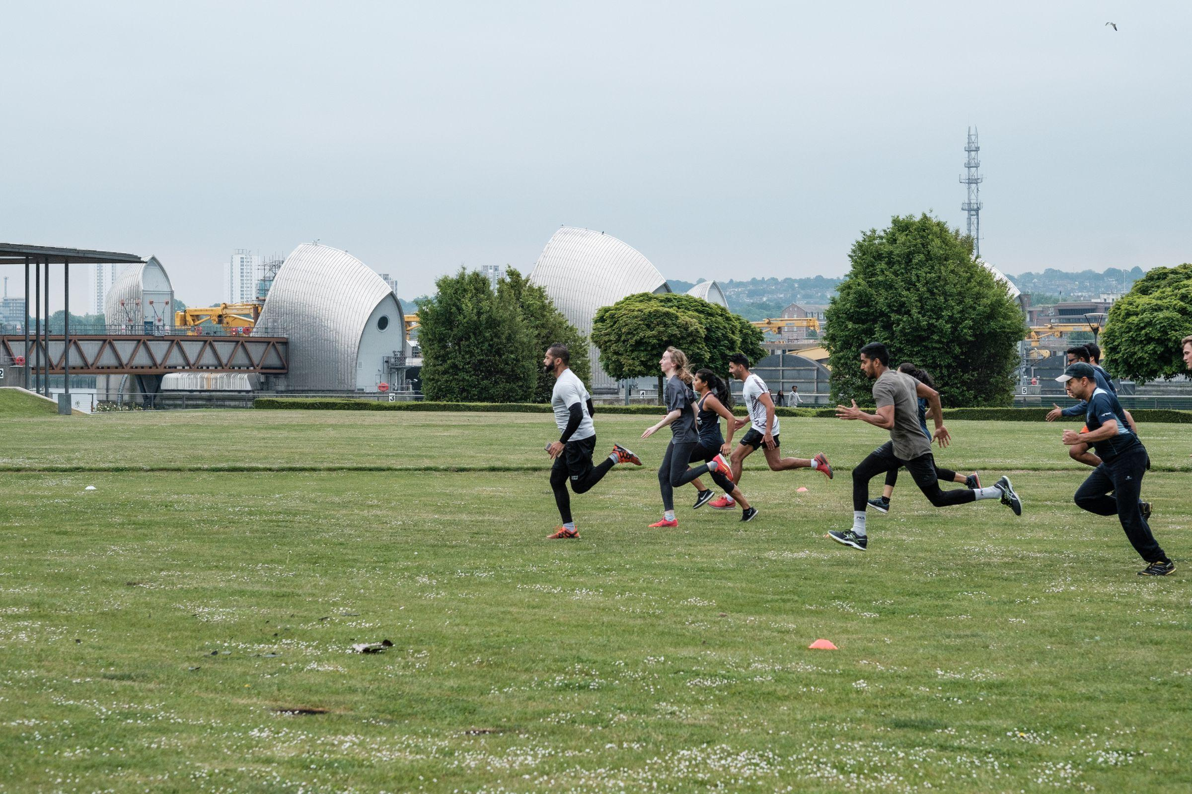 People sprinting across green space with Thames Barrier in the background