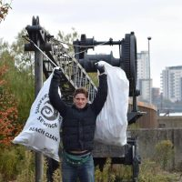 A man holds up two sacks of rubbish above his head