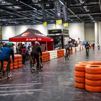 People cycling bikes along an indoor track bordered by tyres