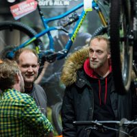 Three men talking by a bike stand