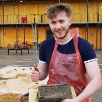 Thomas Wilkinso UEL student holding Brickfield brick