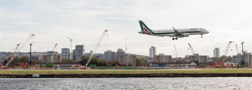 A plane above the runway, seen across the water